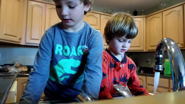 Two Little Boys Washing Dishes Two little boys washing dishes in the kitchen chores stock videos & royalty-free footage