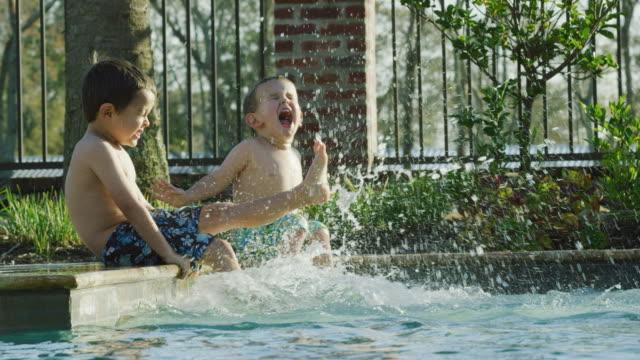 stockvideo's en b-roll-footage met twee kaukasische jongetjes (een drie en een vijf-jarige) zitten langs de kant van een zwembad schoppen hun voeten in het water terwijl glimlachend en lachend op een zonnige dag met een metalen hek achter hen in real time - swimmingpool kids