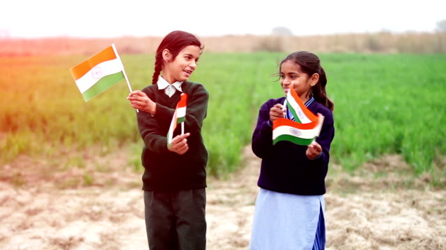 Two little girl waving Indian flag in the nature video
