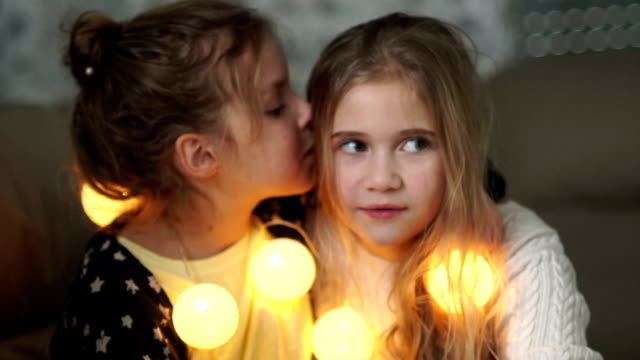 Two little girlfriends share secrets. Girl whispering in her sister's ear, both laughing merrily, christmas evening, new year's garland Two little girlfriends share secrets. Girl whispering in her sister's ear, both laughing merrily, christmas evening, new year's garland cousin stock videos & royalty-free footage