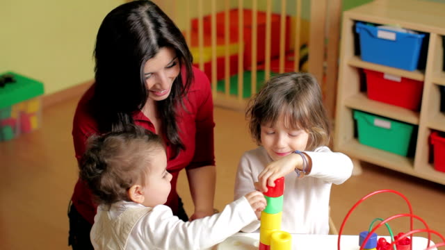 Two little girls and female teacher in kindergarten Female teacher, toddler and 2-3 year girl playing with blocks toy in kindergarten. child care stock videos & royalty-free footage