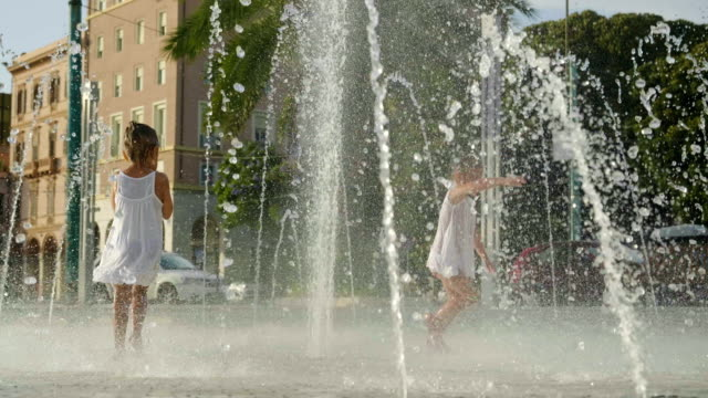 Two little girls are having fun and playing in a fountain, smiling in white dresses, a background of transparent water.