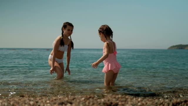 Two little girls are playing in the water on the sunny beach video