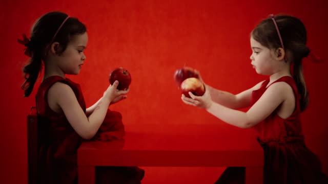 Two little girls eat apples on a red table video