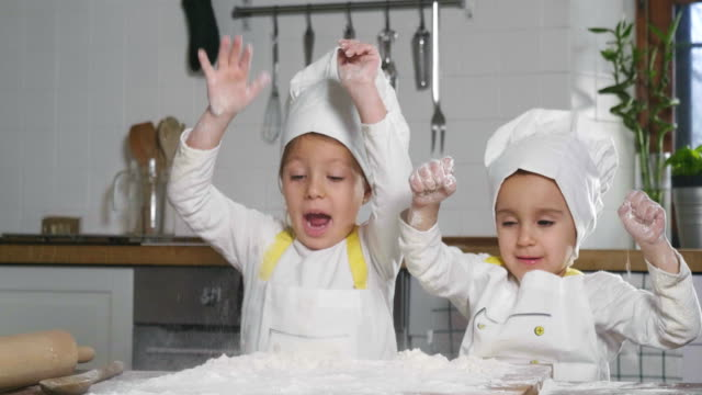 vídeos de stock e filmes b-roll de two little girls in the kitchen prepare food, a dessert for the family. as they learn to cook they start playing with flour and smiling each other. - christmas cooking