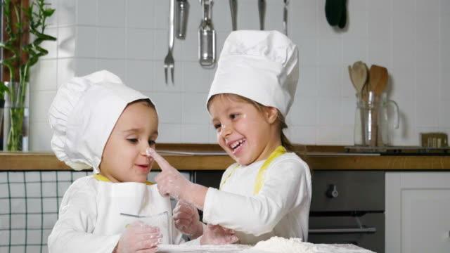 vídeos y material grabado en eventos de stock de dos niñas en la cocina preparan comida, un postre para la familia. como aprender a cocinar empiezan jugando con harina y sonriendo unos a otros. - hermana