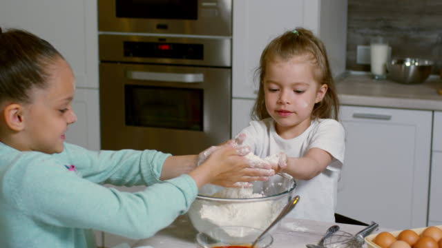 Two Little Girls Learning to Cook Two adorable girls of elementary school age talking to each other while learning to cook and playing with flour in kitchen at home cousin stock videos & royalty-free footage