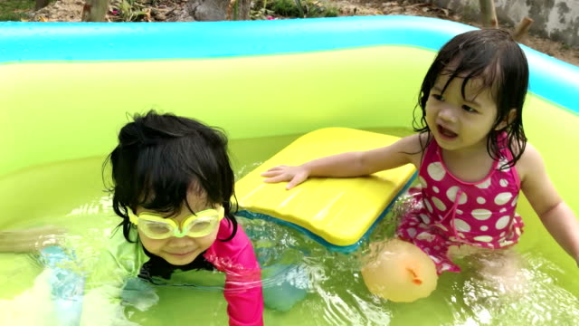 Two little girls playing in the inflatable swimming pool video