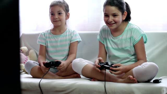 stockvideo's en b-roll-footage met two little girls playing video games - vrijetijdsspel