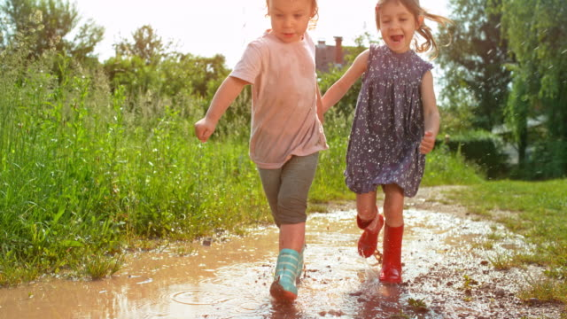 slo mo two little girls running across a muddy puddle while holding hands and laughing - 2 3 anni video stock e b–roll