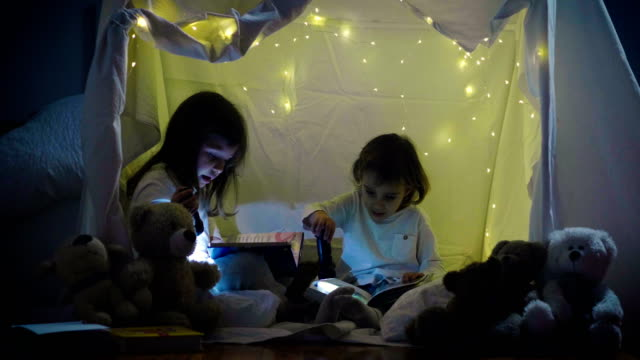 Video Two little girls with mother play at home in the evening to build a camping tent to read books with a flashlight and sleep inside.