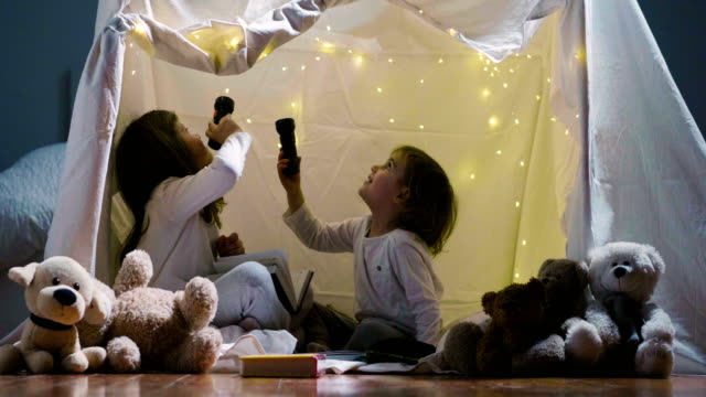 Two little girls with mother play at home in the evening to build a camping tent to read books with a flashlight and sleep inside.