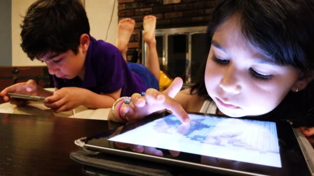 i̇ki küçük çocuk ve oturma odasında gadget'lar ile oynayan kız - bölmek stok videoları ve detay görüntü çekimi