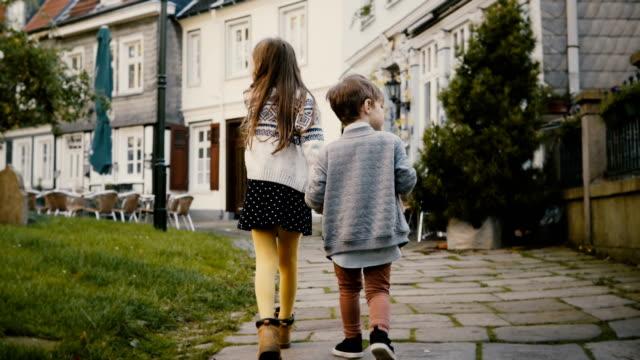 2 つは少し古い建物近く一緒に散歩を子供します。子供、女の子と男の子、美しいドイツの旧市街を散策します。4 k - 兄弟姉妹点の映像素材/bロール