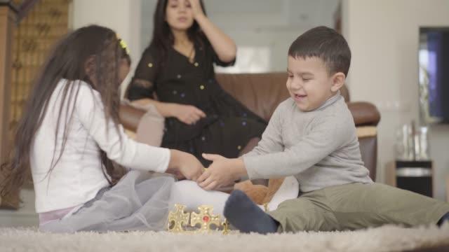 2人の小さな中東の子供たちが前景でおもちゃのために戦い、母親は必死に頭を背景に抱いている - 兄弟姉妹点の映像素材/bロール
