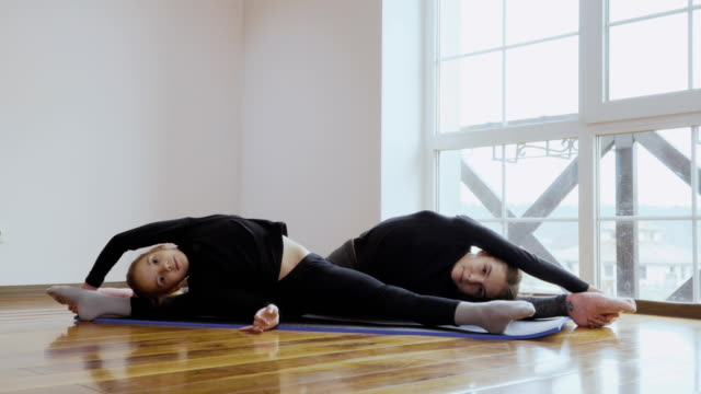 Two little sisters training their flexibility at home video