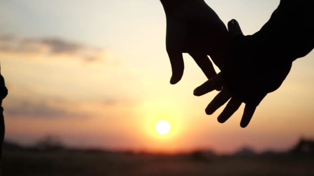 Two lovers joining Hands in 4K Slow motion. Silhouette of Man and Woman holding hands over the Sunset Background. Couple Trust, Love and valentines day concept.