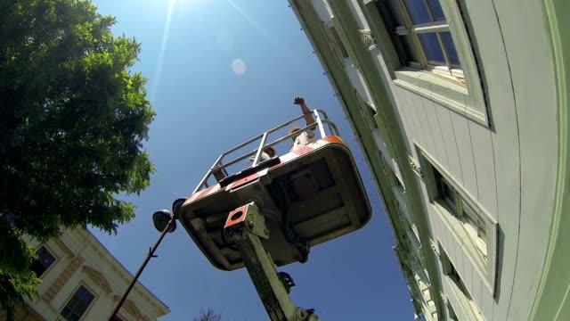 two maintenance workers in the bucket of mobile crane - skylift bildbanksvideor och videomaterial från bakom kulisserna