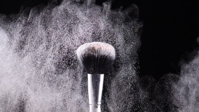 two make-up brushes collide creating an explosion of colored powder 5 - video