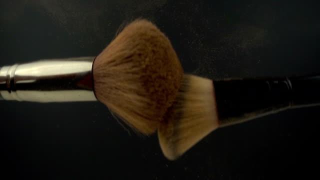 vidéos et rushes de deux pinceaux de maquillage au ralenti. poudre de couleur dorée éclaboussant en frappant une brosse large pour le maquillage à l'autre sur un fond noir. - pinceau à maquillage