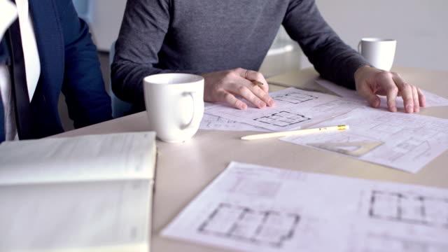 vídeos y material grabado en eventos de stock de dos arquitectos masculinos están examinando los planos del edificio, cerca - plano documento
