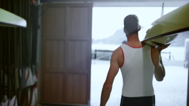 vídeos de stock, filmes e b-roll de slo mo dois atletas masculinos, tomando um barco a remo de rack e a sair da casa da barcos - remo esporte aquático