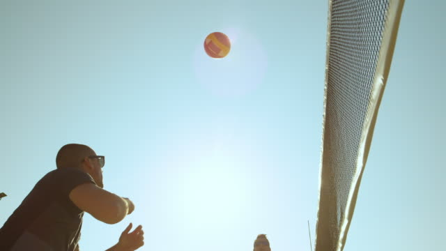 SLOW MOTION: Two male beach volleyball players passing the ball on a sunny day. SLOW MOTION, SUN FLARE, LOW ANGLE, CLOSE UP: Two adult male beach volleyball players passing the ball on a sunny day. Young men having fun playing volleyball during their active summer vacation. beach volleyball stock videos & royalty-free footage