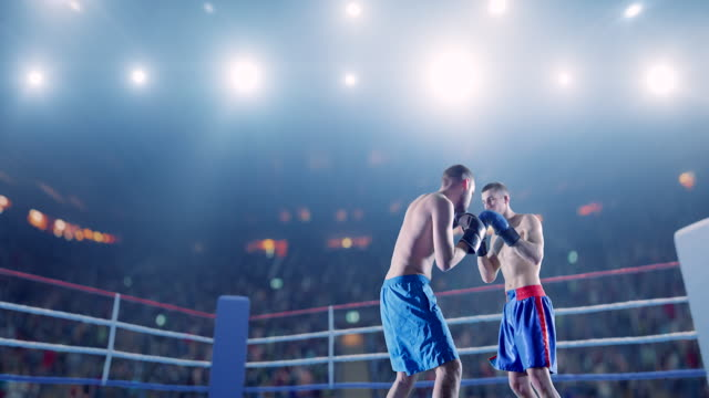 Two male boxers fight on the rink video