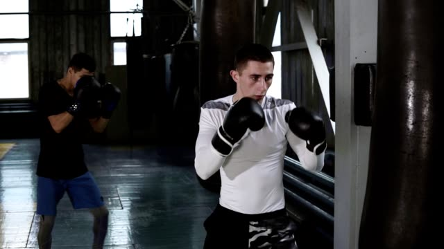 Two male boxers in casual clothes are beating the black boxing pear. Hardworking, training process at boxing gym