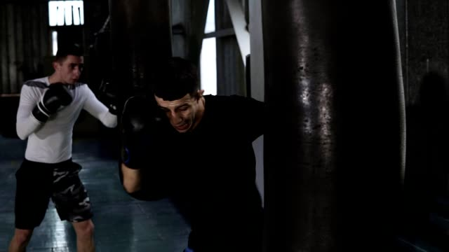 Two male boxers in casual clothes are beating the black boxing pear. Hardworking, training process at boxing gym. Side view