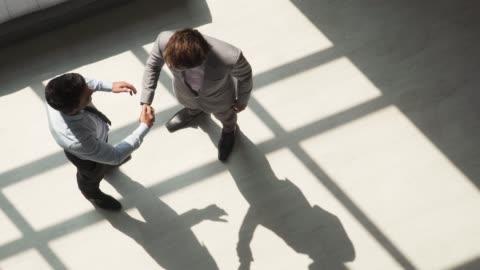 due partner commerciali maschi che si stringono la mano - due persone video stock e b–roll