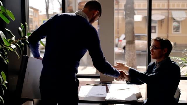 Deux partenaires masculins se réunit au café, salutation, dire Bonjour, serrer la main, assis à table pour discuter de nouveaux projets, l'homme ouvre la mallette, sort de papiers - Vidéo