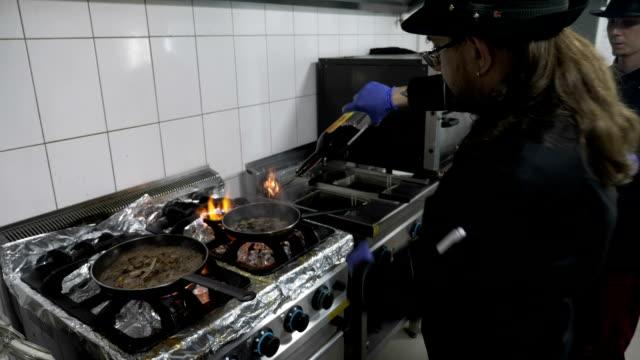 2 男性シェフ鍋完全にワインの追加料理の美味しいレストランのキッチンで肉と野菜のミックスのフランベ - 異国情緒点の映像素材/bロール