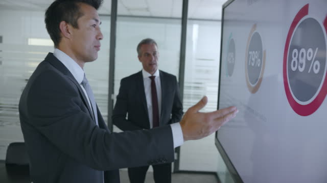 two male colleagues discussing the financial presentation diagrams standing by the large screen in the meeting room - business people stock videos & royalty-free footage