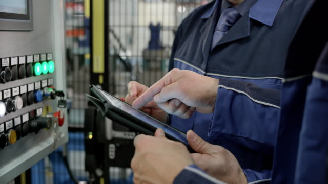 Two male coworkers discussing values shown on the tablet standing by the machine's LCD screen in a factory Medium handheld shot of two male employees standing by a machine in the factory and discussing data on the tablet one of them is holding. Shot in Slovenia. manufacturing equipment stock videos & royalty-free footage