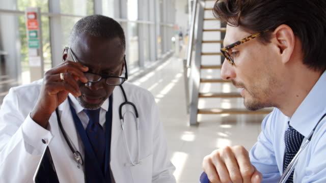 vidéos et rushes de deux médecins de sexe masculin ayant assis autour de la table à l'hôpital de la réunion - equipement médical