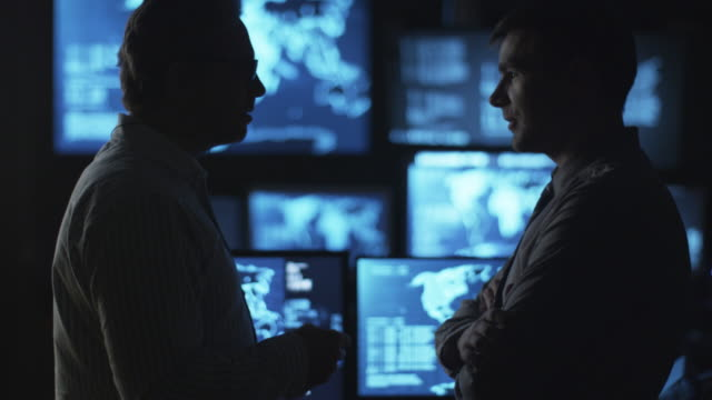 Two male employees are having a conversation in a dark monitoring room filled with display screens. video