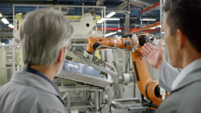 two male engineers inspecting the industrial robots in operation in the factory - automatico video stock e b–roll