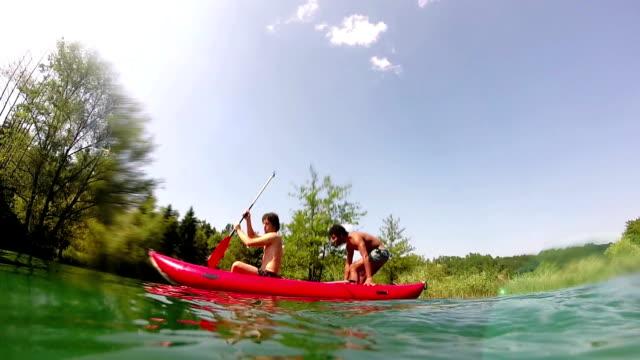 Two male friends having fun in a canoe video