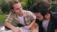 istock Two male friends looking at a map together planning a road trip 1196184105