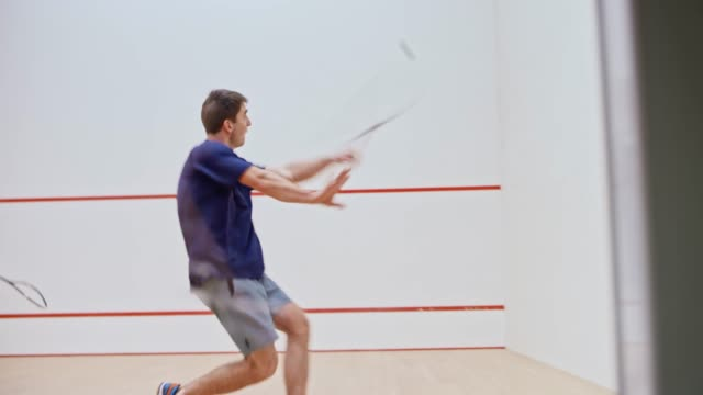 Two male friends playing squash video
