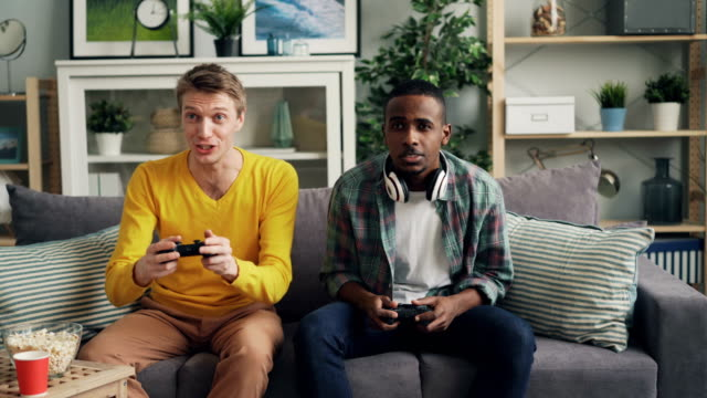 vídeos de stock e filmes b-roll de two male friends playing video game on couch at home - man joystick