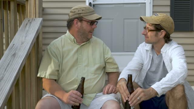 stockvideo's en b-roll-footage met twee mannelijke vrienden praten en iets bespreken terwijl dranken - caravan