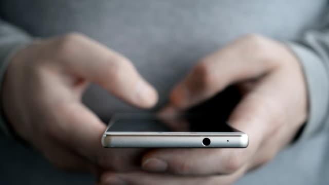 携帯電話で2人の男性の手の速いテキストメッセージsmsメッセージ - メール点の映像素材/bロール