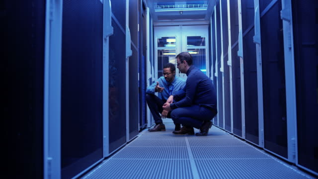 Two male IT technicians crouching by the servers in the server room and checking the operations Wide dolly shot of two male IT technicians checking the servers while crouching in the server room. Shot in Slovenia. server room stock videos & royalty-free footage