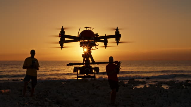 Two male operators controlling drone at sunset