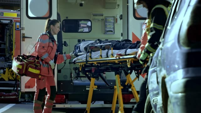 Two male paramedics loading the injured person into the ambulance and the female doctor accompanies the patient video