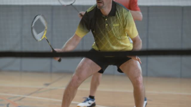 Two male players playing doubles in indoor badminton video