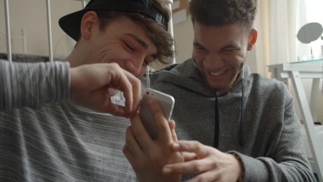två manliga studenter i sovrummet kontrol lera meddelanden på mobil telefoner - unga män bildbanksvideor och videomaterial från bakom kulisserna