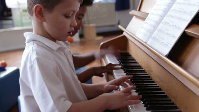 Two Male Students Playing Piano In Music Lesson Together video